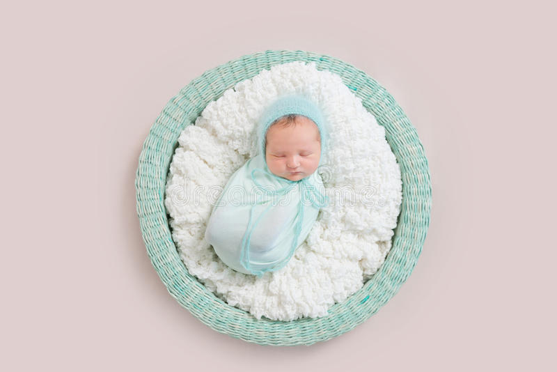Baby wrapped in blue blanket in basket, topview stock photo