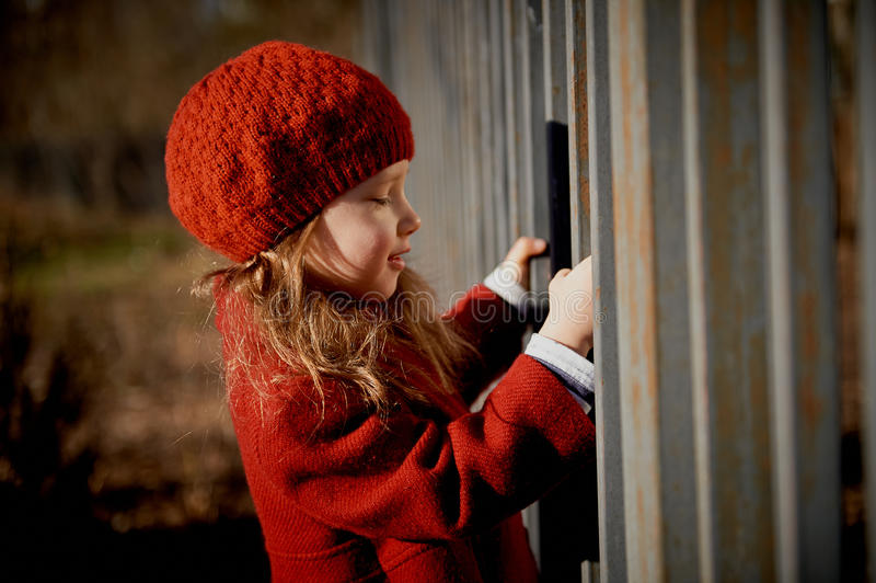 Baby 3 years with long hair.In a red beret and coat stands on the street in the sunshine, near the fence stock image