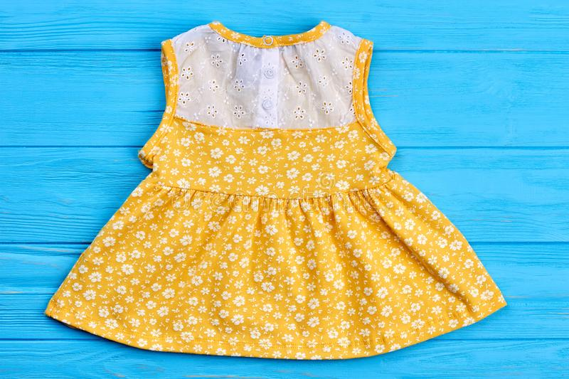 Baby yellow dress with pattern of flowers. stock image