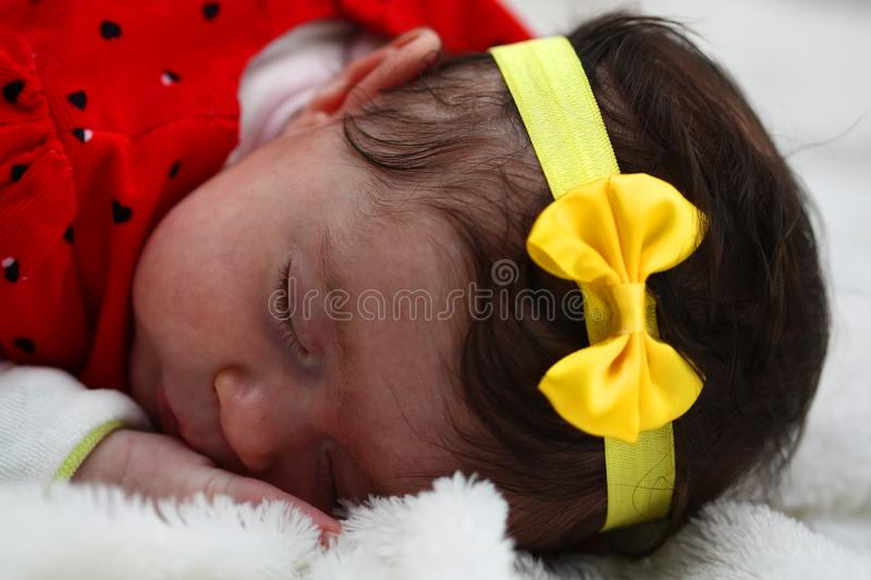 Baby with yelow bow thigh stock photography