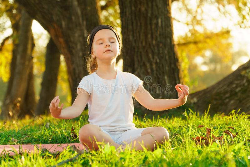 Baby yoga Lotus pose.. a child practicing yoga outdoors stock image