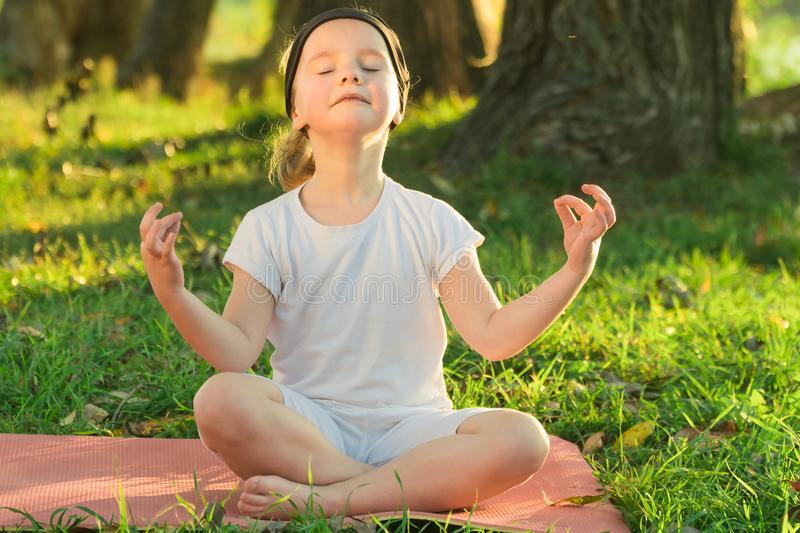 Baby yoga Lotus pose.. a child practicing yoga outdoors stock photo