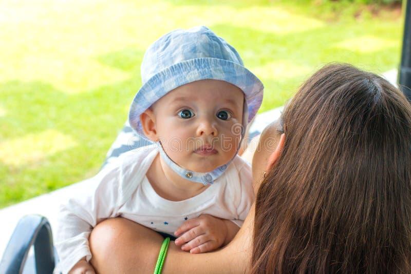Babyansiktestående med nyfiket uttryck och fokuserade blåa ögon ovanför modern som älskar skuldror royaltyfri bild