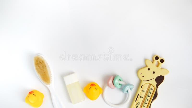 Babybadprodukte lokalisiert auf weißem Hintergrund mit Kopienraum flache gelegte Stück Seife, gelbe Gummiente und Flüssigseife, S lizenzfreie stockfotos