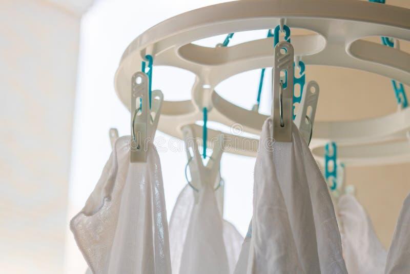 Babybaumwollwindeln, die an der weißen Stoffplastikklammer für Sonne hängen lizenzfreies stockbild
