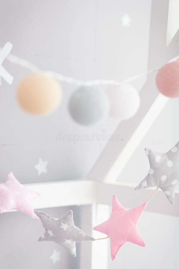 Babybed met vuurradslinger Roze en grijze sterrenslinger in de kinderen` s ruimte stock afbeeldingen