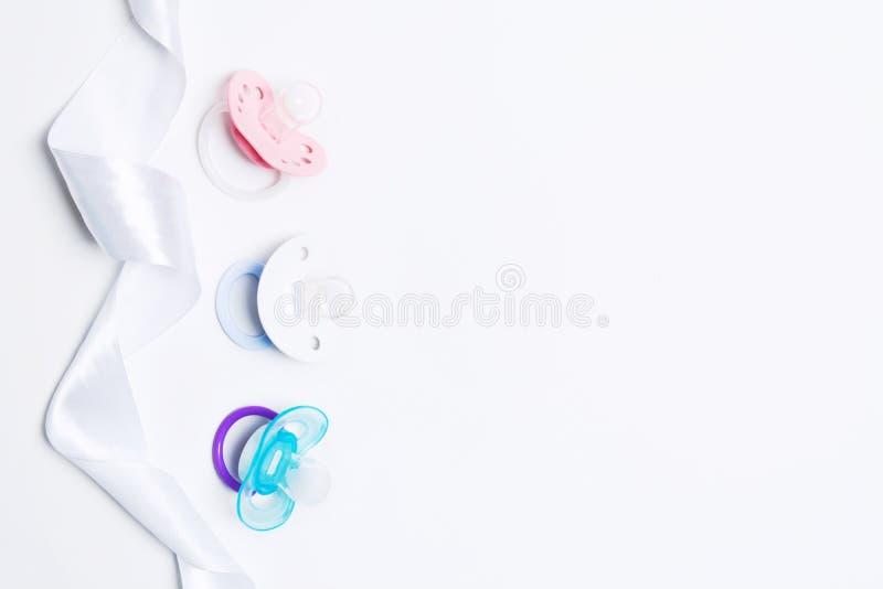 Babydouche met drie de kleurrijke fopspeen van het babysilicone met houder met lint op witte achtergrond Spot omhoog Vlak leg Hoo stock foto's