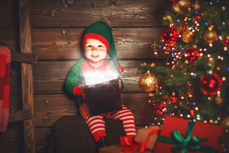 Babyelfenhelfer von Sankt mit einem magischen Weihnachtsgeschenk stockfotografie