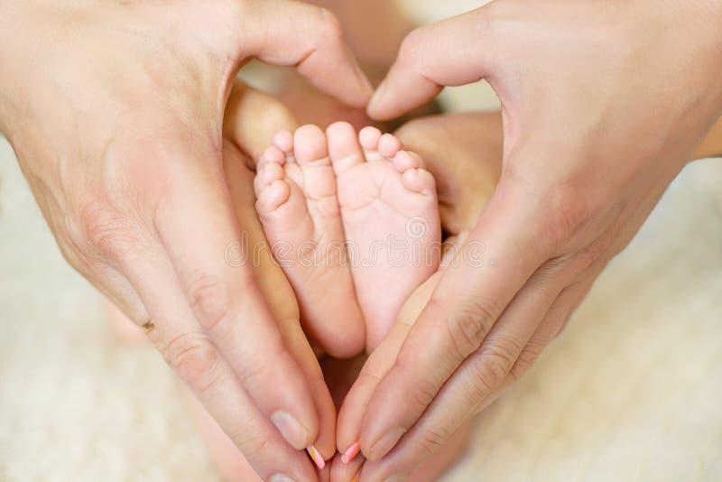 Babyfüße im mom& x27; s und dad& x27; s-Hände mit einem unscharfen Hintergrund lizenzfreie stockbilder
