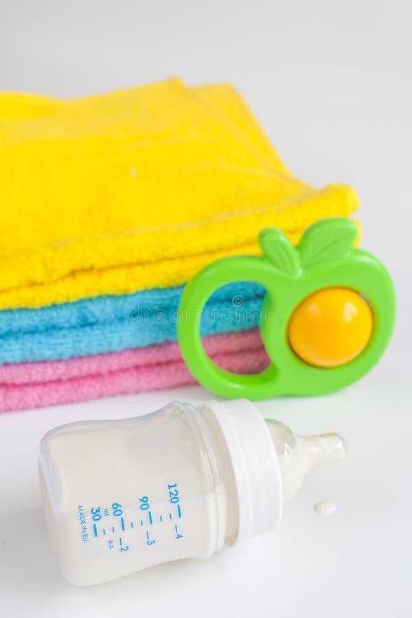 Babyflasche mit Milch und Tuch auf weißem Hintergrund lizenzfreie stockbilder