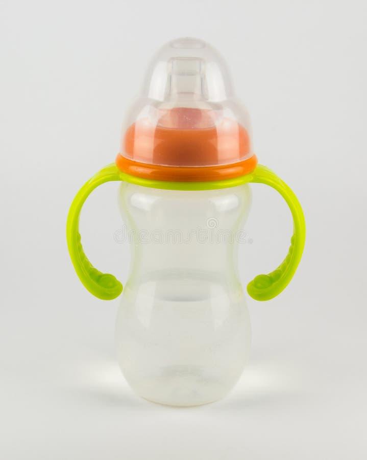 Babyflasche mit Wasser auf einem weißen Hintergrund lizenzfreies stockbild