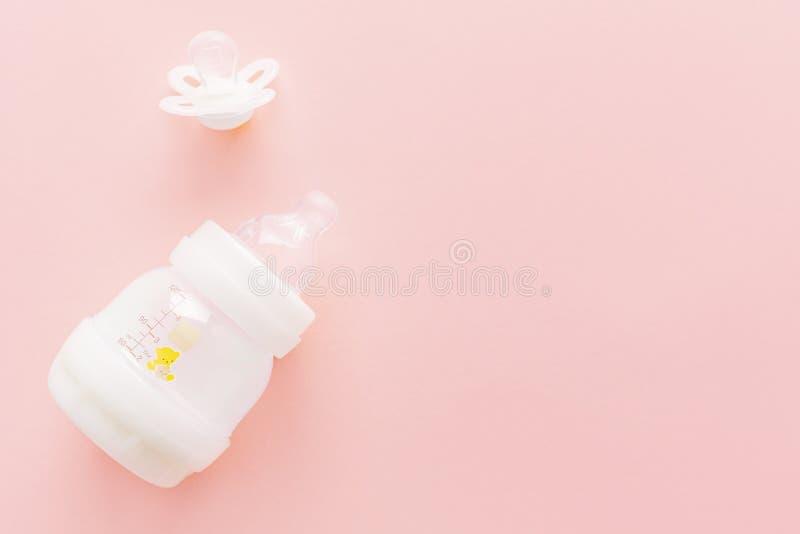 Babyflasche und -nippel auf Rosa lizenzfreies stockbild