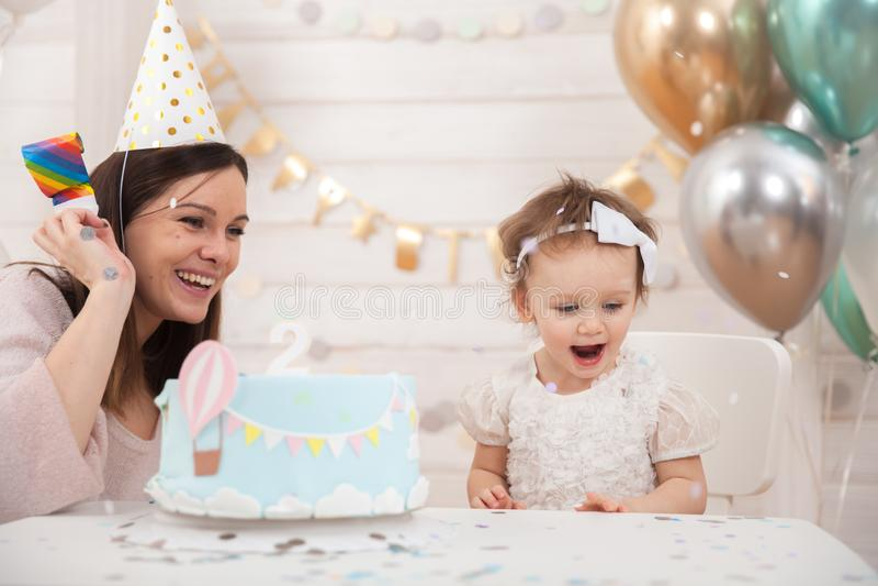Babygeburtstagsfeier Mutter und ihre Tochter feiern und Spaß zusammen Kinderpartei mit Ballondekoration und -kuchen lizenzfreies stockbild