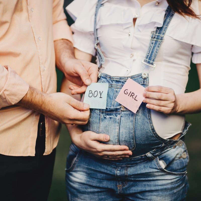 Babygeschlecht Mutter und Vati mit JUNGEN- und MÄDCHEN-Karten lizenzfreie stockfotos