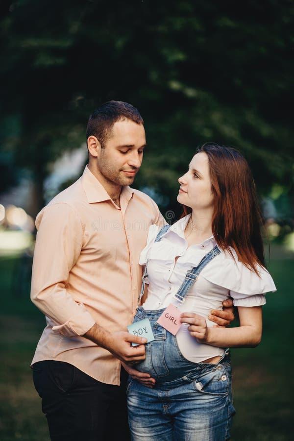 Babygeschlecht Mutter und Vati mit JUNGEN- und MÄDCHEN-Karten lizenzfreies stockfoto