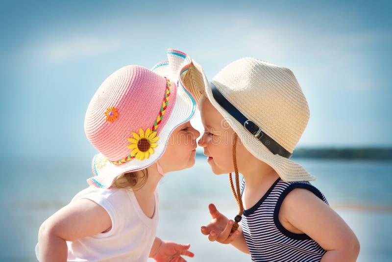 Babygirl和babyboy亲吻在海滩 免版税库存图片