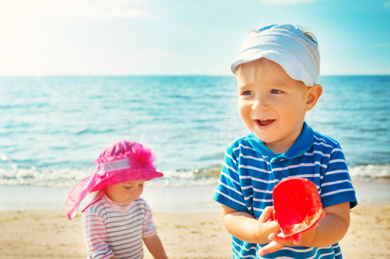 Babygirl and babyboy playing on the beach stock photos