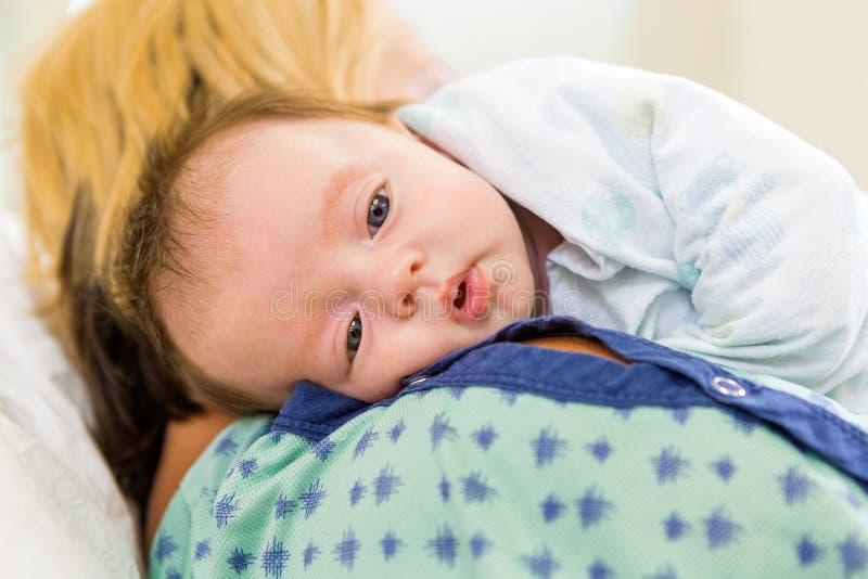 Babygirl sveglio che riposa sulla spalla della madre dentro fotografia stock libera da diritti