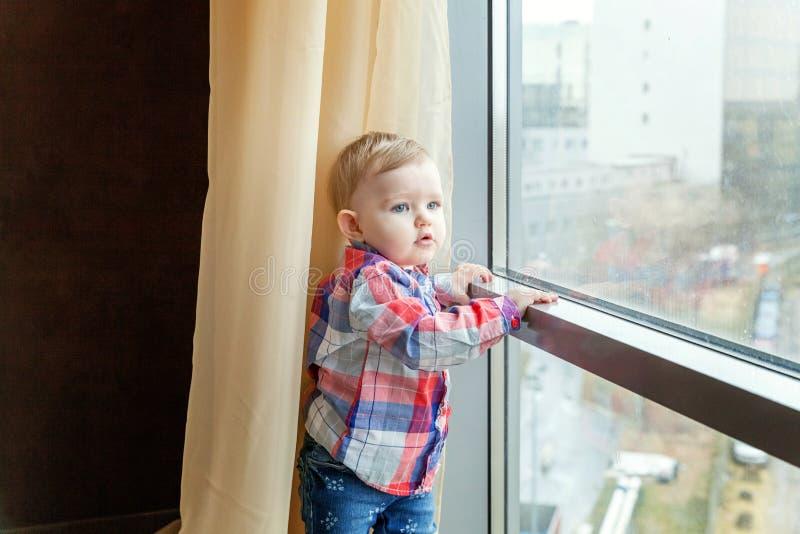 Babyglimlachen in een ruimte dichtbij het venster stock fotografie