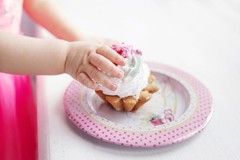 Babyhand, die den ersten Geburtstagskuchen hält stockfoto