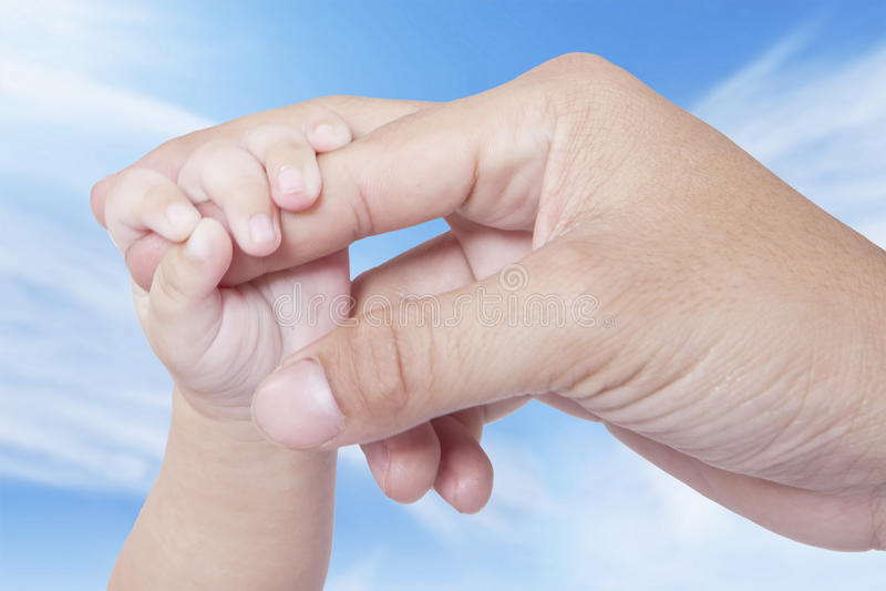 Babyhand die vadervinger begrijpen stock foto's