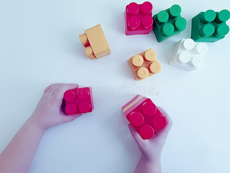 Babyhandspielen bunt mit plasticconstruction Blöcken auf weißem Hintergrund lizenzfreie stockfotos