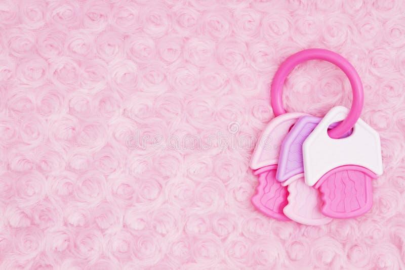 Babyhintergrund mit einem Beißring auf blassem - rosa rosafarbenes Plüschgewebe stockfoto
