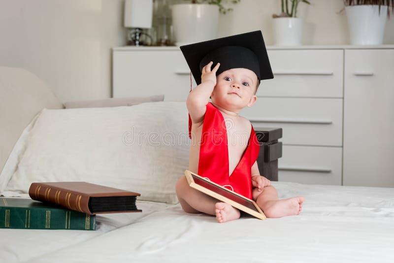 Babyjongen in de zitting van de academicusbaret op bed en het kijken I royalty-vrije stock foto's