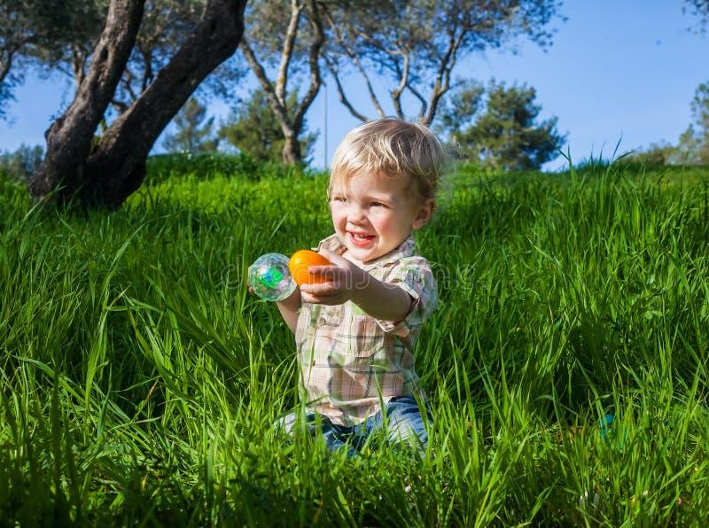 Babyjongen die een ei standhouden royalty-vrije stock afbeeldingen
