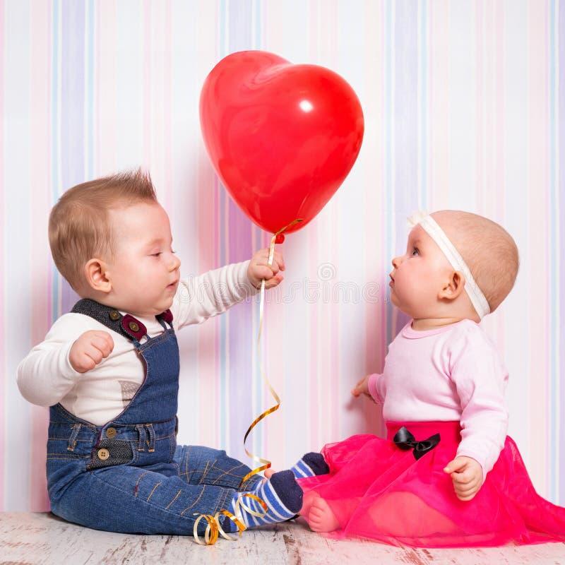 Babyjongen die een hartballon geven aan het meisje stock afbeelding