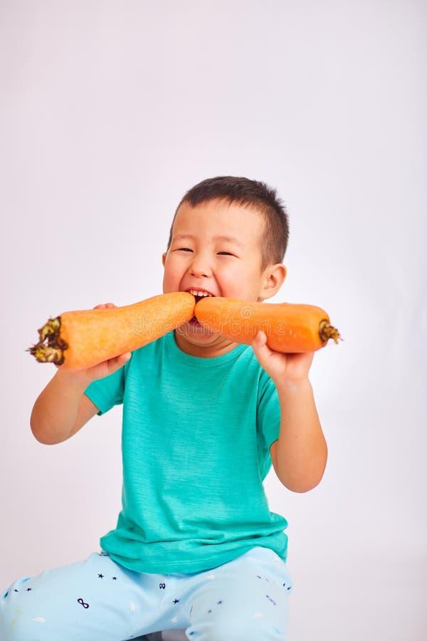 Babyjongen die in een turkoois overhemd, reusachtige wortelen eten - vruchten en gezond voedsel royalty-vrije stock foto
