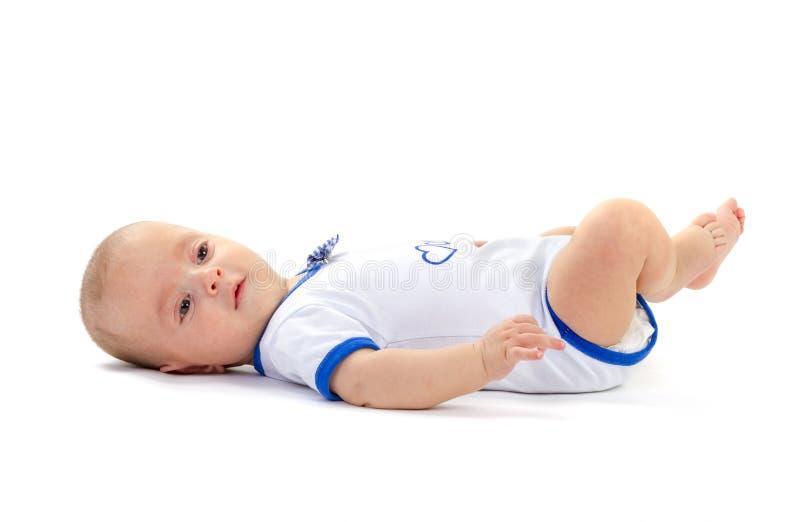 Babyjongen die op witte vloer liggen royalty-vrije stock fotografie
