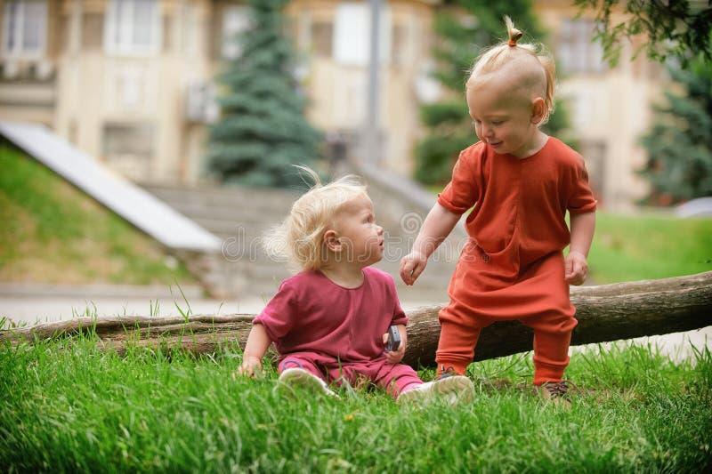 Babyjongen en babymeisje die terwijl het zitten op groen gras spelen stock fotografie