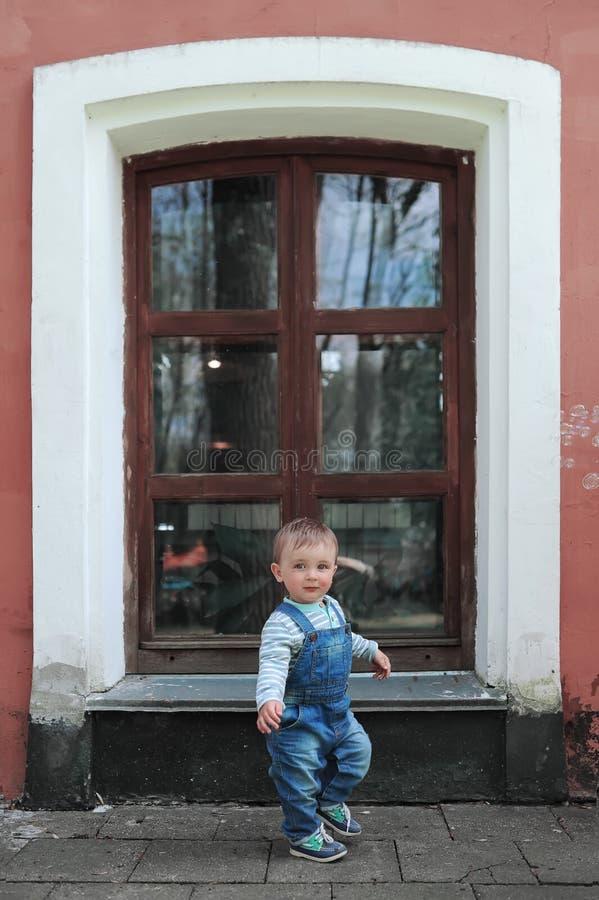 Babyjongen en groot venster in stadspark stock afbeelding