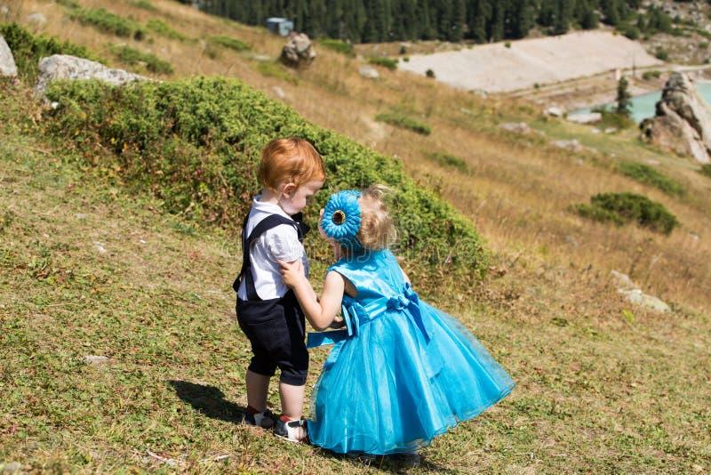 Babyjongen en het aanbiddelijke kindmeisje kussen op gras De zomer groene aard stock afbeelding