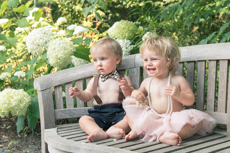 Babyjongen en meisje in formele kledingzitting op houten bank in een mooie tuin stock fotografie