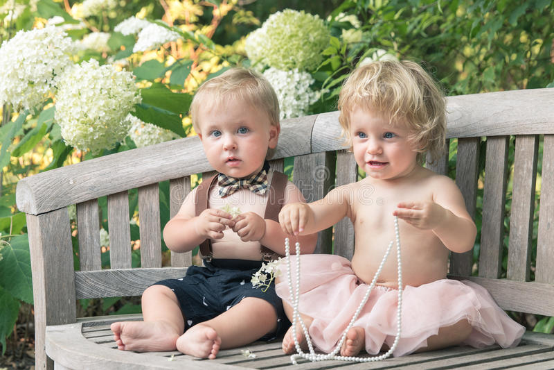 Babyjongen en meisje in formele kledingzitting op houten bank in een mooie tuin stock foto's