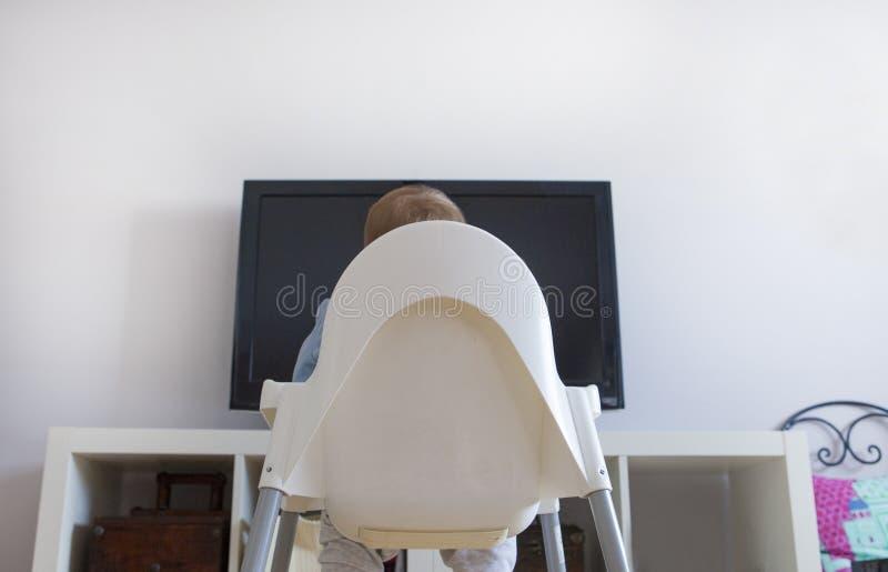 Babyjongen het letten op TV van Kinderen programma's stock foto's