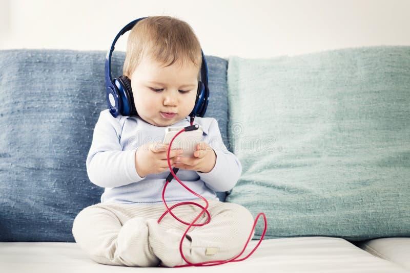 Babyjongen het luisteren muziek bij oortelefoons met iphone in handen. royalty-vrije stock afbeelding