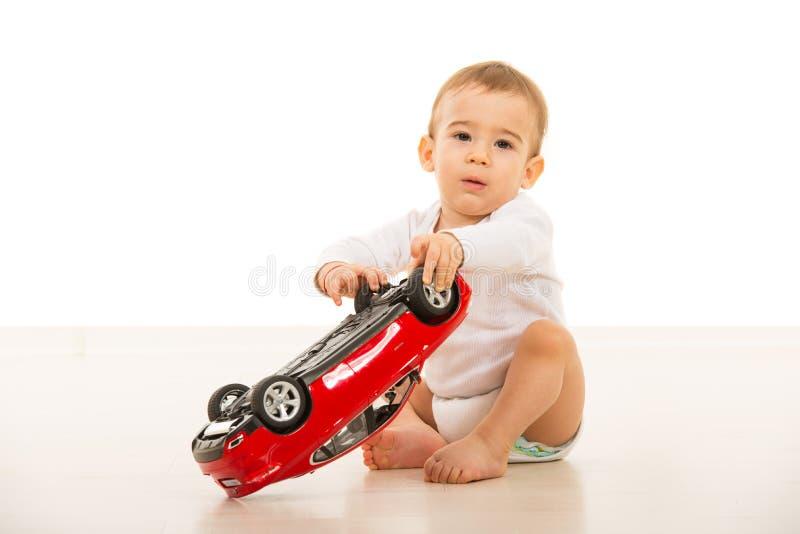 Babyjongen het spelen met autostuk speelgoed stock foto's