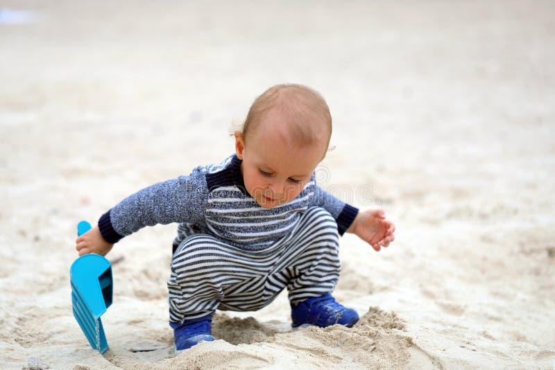 Babyjongen het Spelen met Zand en Blauwe Plastic Schop op het Strand stock fotografie