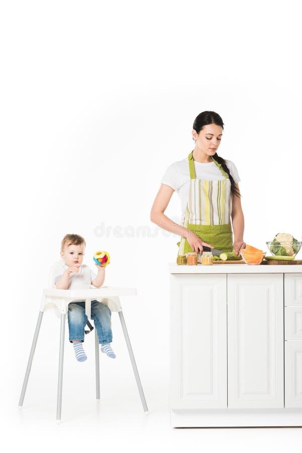 babyjongen in highchair met stuk speelgoed en moeder scherpe courgette bij lijst royalty-vrije stock afbeelding