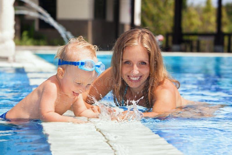 Babyjongen met moeder die met pret in de pool zwemmen stock foto's