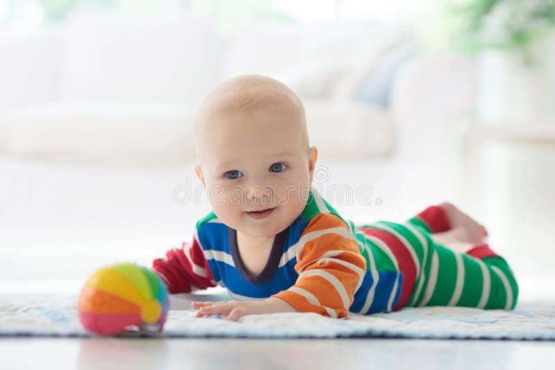 Babyjongen met speelgoed en bal stock foto's