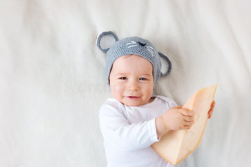 Babyjongen in muishoed die op deken met kaas liggen stock fotografie
