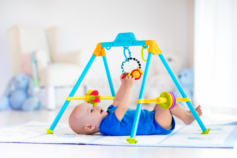 Babyjongen op spelmat Kind het spelen in gymnastiek stock afbeelding