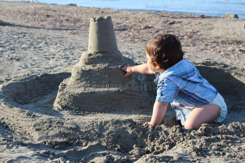 Babyjongen op strand het spelen met zand stock foto