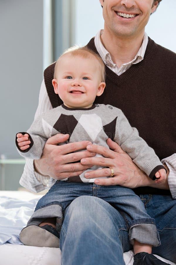 Babyjongen op zijn vadersknie die wordt gezeten royalty-vrije stock afbeeldingen