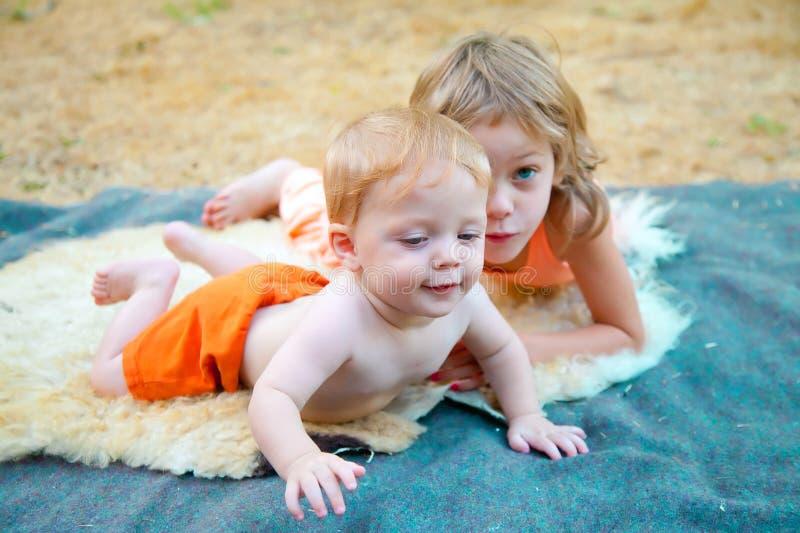 Babyjongen in openlucht met zijn zuster stock foto