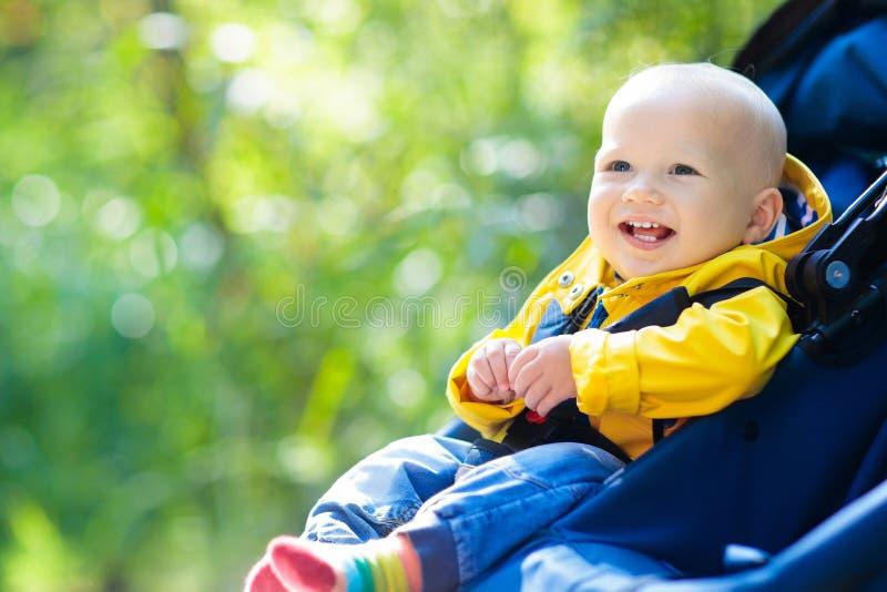 Babyjongen in wandelwagen in de herfstpark royalty-vrije stock fotografie